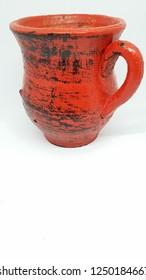 red pottery mug isolated on white background closeup studio image