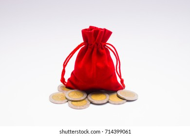 Red pouch and coins on white background.