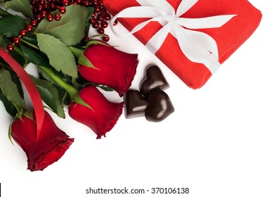 Red present box with white ribbon, red roses and candies in a shape of a heart isolated on white background