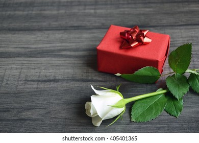 Red present and white rose