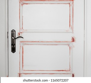 Red primer dapping on white solid wood door, filler for gap and smoothen surface