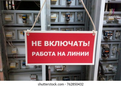 "Red prohibitory sign ""Do not switch on! Work on the line"" on the background of electrical equipment. Translation of the inscription from the Russian language."