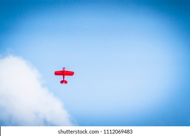 Red propeller plane flying upwards on a blue heaven with white clouds