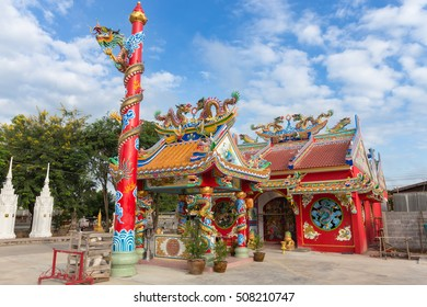 Red public shrine with golden dragon statue in chinese style on blue sky background at Thailand