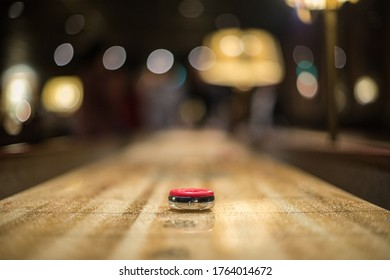 Red puck approaching the 3 point zone of a shuffleboard table