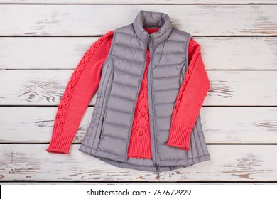Red pullover and gray vest on wooden display at the store. Bright color pairing for dismal autumn weather. Autumn fashion trends.