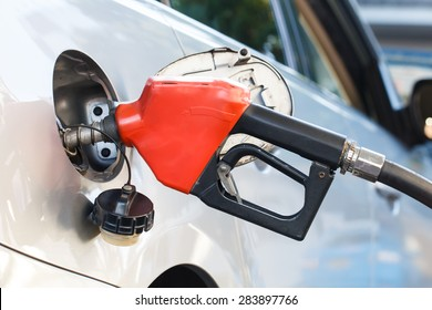 Red pumping fuel oil in car at gas station-2
