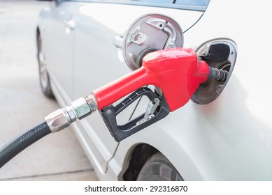 red  pumping gasoline fuel in car at gas station