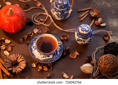 red pumpkin on a wooden table with autumn dry flowers and rassian gzhel dishes