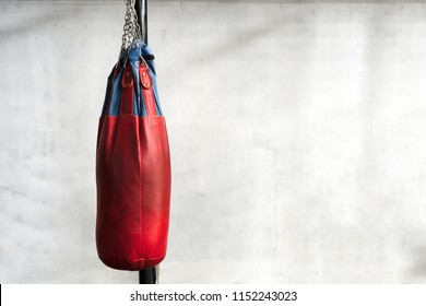 Red punching bag is hanging on cement wall in boxing gym. Sport, Lifestyle and healthy concepts. Sandbag on concrete wall for punch kick and kick. Thai boxing sport.
