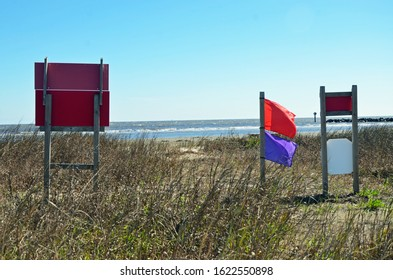 Red and purple beach warning flags flying in the wind near the coast warning people of the dangers in the water.