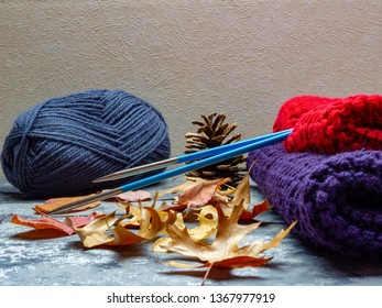 Red and purple knitting with blue needles with fall decoration of fall leaves and a pine cone.