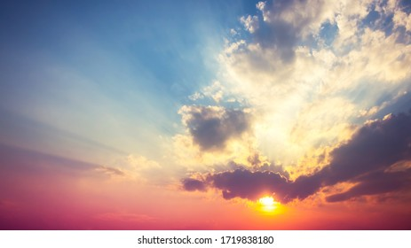 red purple with orange sunset in overcast blue sky with sun rays light