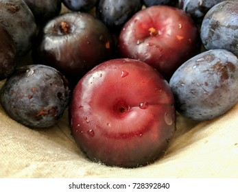 red and purple plums in fruit basket