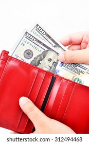 Red purse with US dollars in the hands on a white background