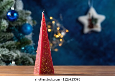 Red pyramid candle with golden decoration and christmas tree in the background on a wooden table
