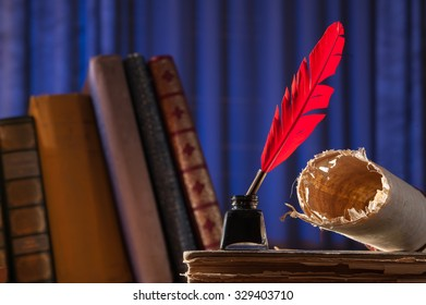 Red quill pen, black inkwell and a rolled papyrus sheet enlightened by a candle on a blue background
