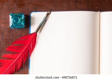 Red quill pen and green inkwell on an open sketchbook