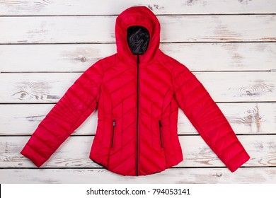 Red quilted down jacket on wooden wall. Hood with elastic piping and strong zippers. Stylish outerwear for women.