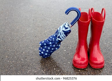 Red rain boots and polka dot umbrella on wet pavement