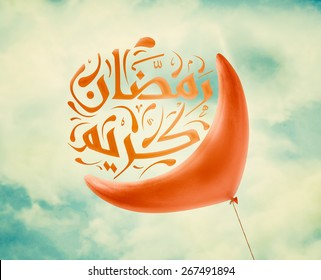 Red Ramadan crescent balloon in vintage blue sky with clouds, Arabic Islamic calligraphy of text Ramadan Kareem.