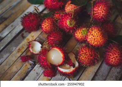 Red rambutan Nephelium lappaceum on broun board.  Fruit tropical tree of the family Sapindaceae , native to South - East Asia , cultivated in many countries in the region