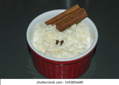 red ramekin with traditional sweet of parties of Sao Joao in June, white canjica mungunza or munguza, typical Brazilian food