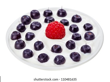 Red raspberry and blue bilberry in small round plate with sour cream, isolated on white