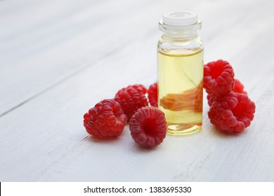 Red Raspberry Oil container with fresh raspberry glass bottle on white wooden background