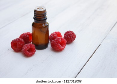 Red Raspberry Oil container with red raspberry glass jar on wooden background