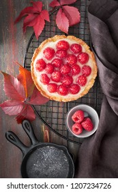 Red raspberry shortbread tart with vanille custard and glazed fresh raspberries on cooling rack over dark brown wooden rustic background. Top view