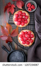 Red raspberry shortbread tarts with vanille custard and glazed fresh raspberries on cooling rack over dark brown texture background. Top view
