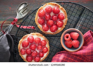 Red raspberry shortbread tarts with vanille custard and glazed fresh raspberries on cooling rack on dark brown wood, top view