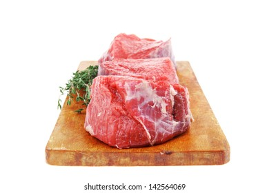 red raw fillet chops : three fresh beef meat chops with thyme twig on wooden plate . isolated over white background