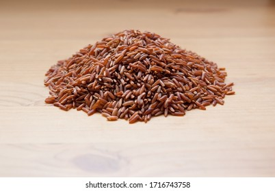 Red raw rice on a wooden background. Healthy food.