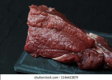 Red raw veal meat on gray ceramic rain. Delicious food for your recipes on a dark background.