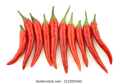red rawit peppers (Capsicum annuum 'Bird's Eye') in a row on a white background