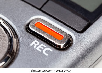 Red REC recording button on a modern pocket audio voice recorder, switch object macro extreme closeup Secretly recording, journalist or reporter equipment, simple live music recording abstract concept