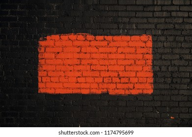 A red rectangle painted on a black brick wall which forms a frame around the red