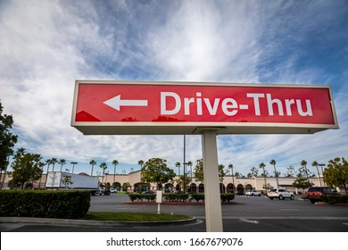 Red rectangular sign reading Drive Thru for fast food retaurant against blue sky and clouds