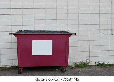 Red recycling dumpster against a white block wall
