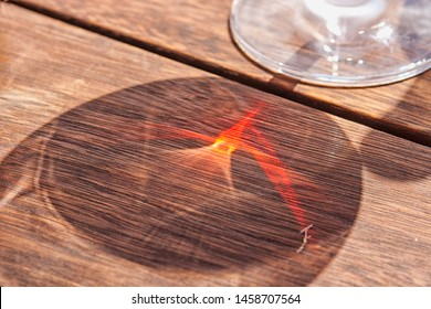 Red reflection through glass of red wine on wooden table