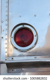 Red reflector on corner of vintage metal camper trailer caravan detail