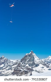 Red rescue helicopter with basket on the Matterhorn mountain
