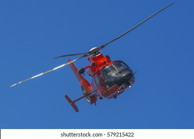 Red rescue helicopter in flight with a blue sky
