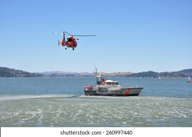 A red rescue helicopter and gray rescue boat in the water
