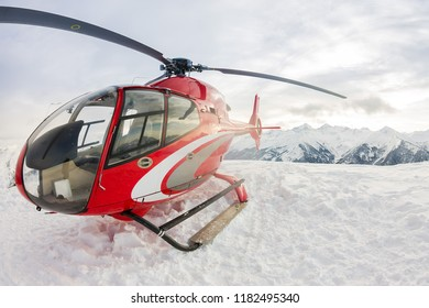 Red rescue helicopter lands standing in snowy mountains