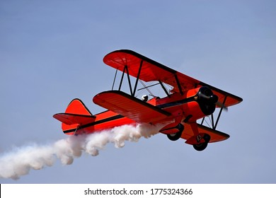 Red retro airplane (biplane) isolated on blue sky background. Vintage old red airplane & pilot flying in sky. View of red airplane & white smoke. Biplane condensation trail, smoky effect after plane