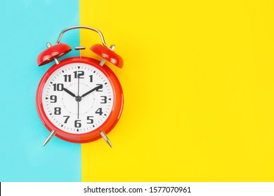Red retro alarm clock with a big dial, on divided blue-yellow background. The concept of time, delay, morning rise, the appointed meeting. Layout with copy space for your text. Flat layout, top view.