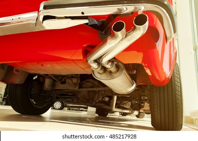 Red retro car exhaust system. Auto exterior detail with sunlight
